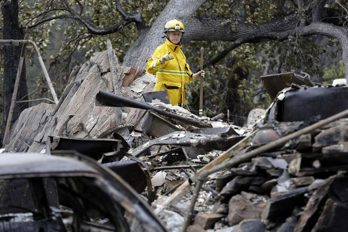 Cadaver search dog handler Lynne Engelbert looks over the remains of a home in the Anderson Springs area of a man missing following a wildfire days earlier Wednesday, Sept. 16, 2015, near Middletown, Calif. Aided by drought, the flames have consumed more than 100 square miles since the fire sped Saturday through rural Lake County, less than 100 miles north of San Francisco. Cooler weather helped crews gain ground and the fire was 30 percent contained Wednesday. (AP Photo/Elaine Thompson)