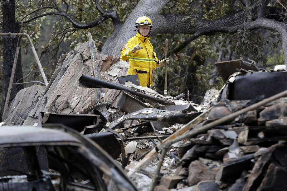 Cadaver search dog handler Lynne Engelbert looks over the remains of a home in the Anderson Springs area of a man missing following a wildfire days earlier Wednesday, Sept. 16, 2015, near Middletown, Calif. Aided by drought, the flames have consumed more than 100 square miles since the fire sped Saturday through rural Lake County, less than 100 miles north of San Francisco. Cooler weather helped crews gain ground and the fire was 30 percent contained Wednesday. (AP Photo/Elaine Thompson) Photo: Elaine Thompson, Associated Press