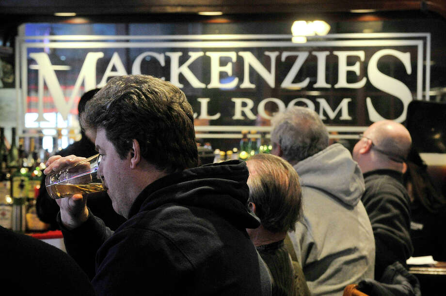 "Craig Robinson enjoys a drink at the bar of Mackenzie's Grill Room in Old Greenwich neighborhood of Greenwich, Conn., on Sunday, March 1, 2015. Robinson remembers going to the bar in the late 1970s when it was called Tracks, moved away for a time, and moved back across the street and has been a regular since the late 1990s. ""It's an Old Greenwich landmark,"" says Robinson. Photo: Jason Rearick / File Photo / Stamford Advocate"