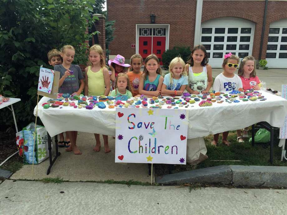 "Local children raised more than $600 for the charity ""Save the Children"" of Syria by collecting rocks from the beach, painting them and selling them over the weekend. The first day, the youngsters, shown here, put their outside the fire station in Old Greenwich on Sound Beach Avenue. Photo: Contributed / Contributed Photo / Greenwich Time Contributed"