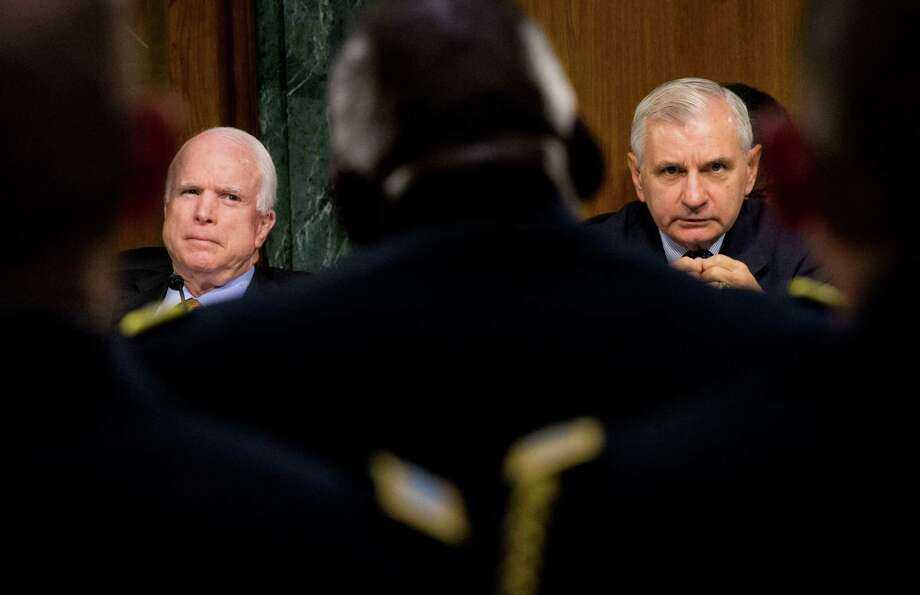Armed Services Committee Chairman Sen. John McCain, left, and the committee's ranking member, Sen. Jack Reed, on Wednesday discuss U.S. military operations to counter the Islamic State in Iraq during the committee's hearing on Capitol Hill in Washington.  Photo: Pablo Martinez Monsivais, STF / AP