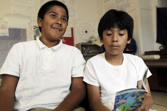 From left, Marciano Antone, 10, and Brian Pacheco, 10, read their poem together during a portrait at Sanchez Elementary School in San Francisco, Ca. on Wednesday, September 16, 2015. As a part of Writers Corps, last year the group of now fifth graders wrote poems reacting to the murals in the Mission District. The book of poetry was published in June of this year.