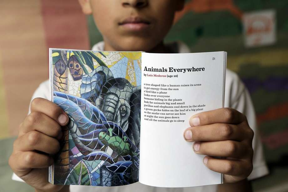 "Luis Mederos, 10, is pictured with his poem, ""Animals Everywhere,"" and a picture of the mural that inspired it, at Sanchez Elementary School. Photo: Dorothy Edwards, The Chronicle"