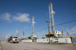 Over thirty oil drilling rigs are idle in a Helmerich & Payne, Inc. yard along Groening Street in Odessa, Texas, as rig counts drop in the Permian Basin, Monday, May 18, 2015. (Courtney Sacco/Odessa American via AP)