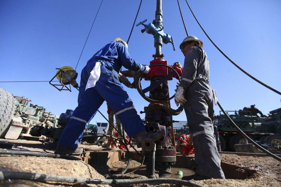 Oil field workers at a well being fracked south of Midland. Photo: New York Times