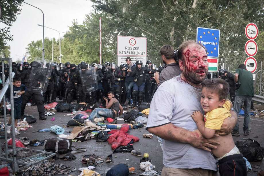 Hungarian riot police unleash tear gas and water cannons against hundreds of migrants on Wednesday after they broke through a razor-wire fence at the Horgos border crossing in Serbia. Photo: SERGEY PONOMAREV, STR / NYTNS