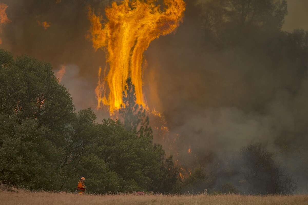 SAN ANDREAS, CA - SEPTEMBER 13: Tall flames rise behind a firefighting inmate hand crew member at the Butte Fire are seen on September 13, 2015 near San Andreas, California. California governor Jerry Brown has declared a state of emergency in Amador and Calaveras counties where the 100-square-mile wildfire has burned scores of structures so far and is threatening 6,400 in the historic Gold Country of the Sierra Nevada foothills. (Photo by David McNew/Getty Images) *** BESTPIX ***