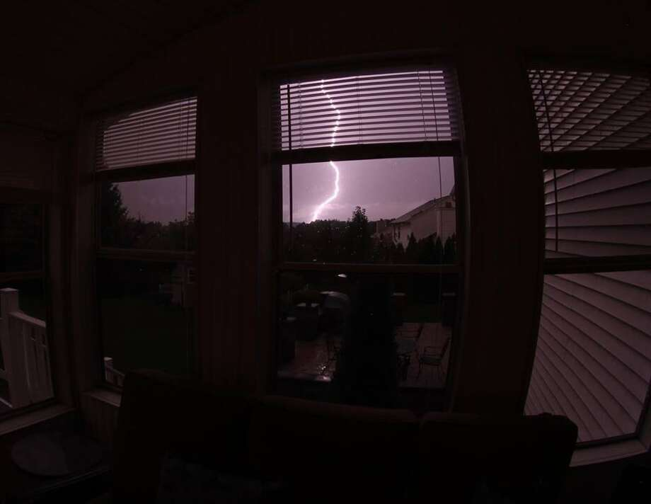 A fish-eye lens captures a lightning bolt from a Colonie window during a summer thunderstorm. (James Condon)