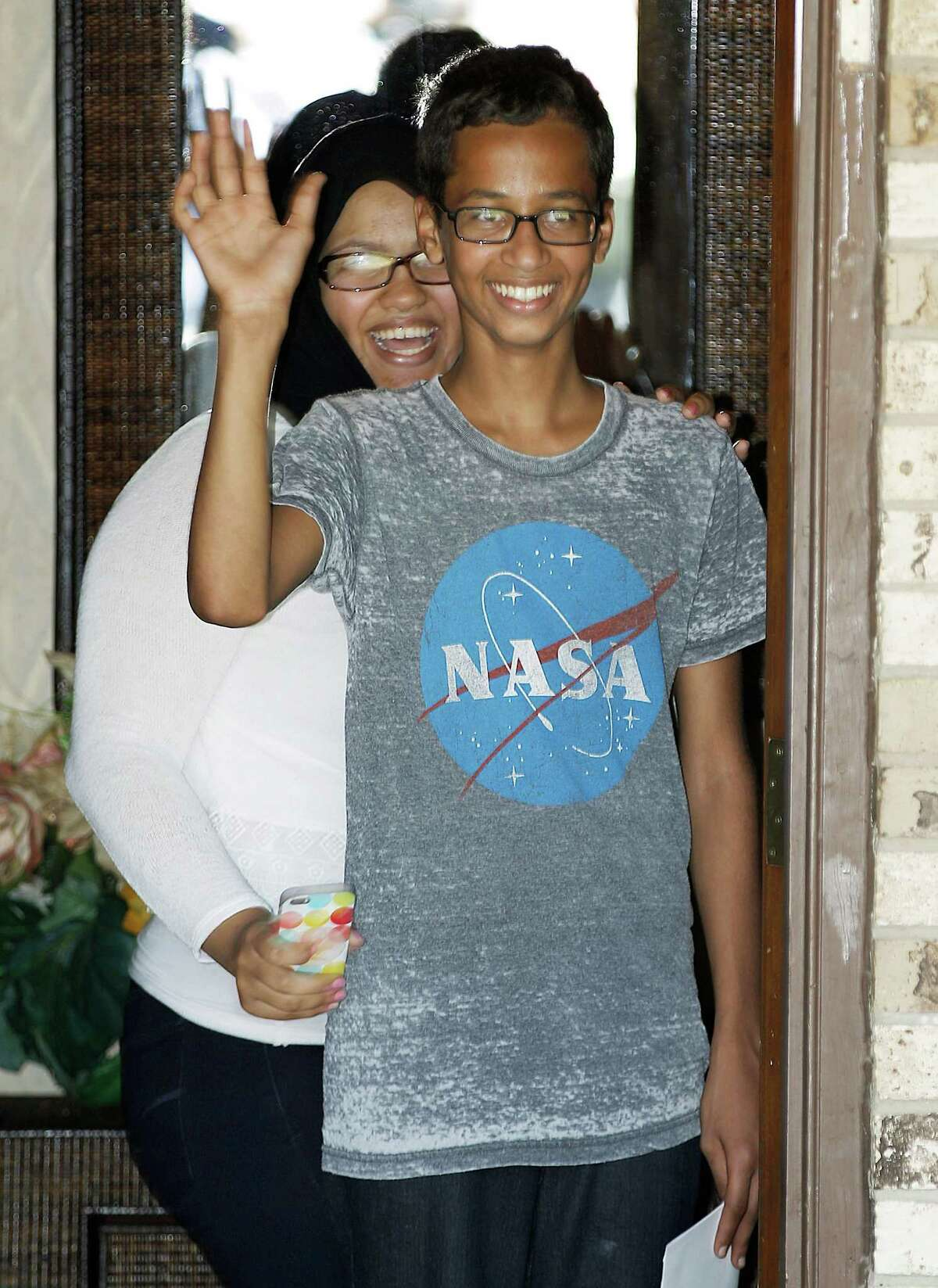 Ahmed Mohamed, 14, right, waves to the media from the front door of his house as his sister, Eyman Mohamed, looks on in Irving. Ahmed was accused of building a hoax bomb.