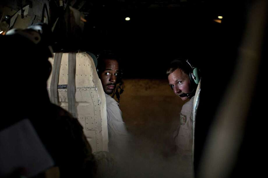 In this Thursday, Sept. 10, 2015 photo, members of a cargo aircraft crew perform a visual check of their passengers as their plane prepares to land on the USS Theodore Roosevelt aircraft carrier currently deployed in the Persian Gulf, supporting Operation Inherent Resolve, the military operation against Islamic State extremists in Syria and Iraq. (AP Photo/Marko Drobnjakovic) Photo: Marko Drobnjakovic, STR / AP