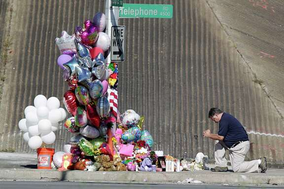 A man prays at the scene where a Houston Independent School District bus was in an the accident that killed two students.