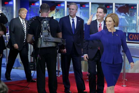 Republican presidential candidate, businesswoman Carly Fiorina, right, leads fellow candidates Scott Walker, second from right, Jeb Bush, center, and Donald Trump as they take the stage prior to the CNN Republican presidential debate at the Ronald Reagan Presidential Library and Museum on Wednesday, Sept. 16, 2015, in Simi Valley, Calif. (AP Photo/Chris Carlson)