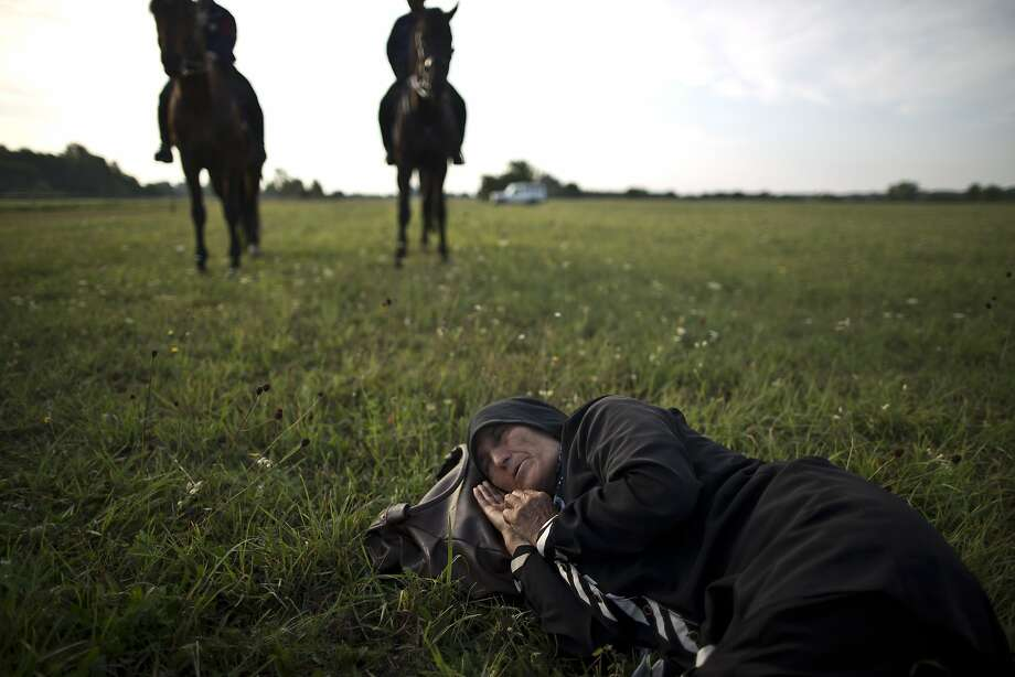 An elderly Afghan migrant rests on the ground of a field while she and others being detained by Hungarian police on horses for sneaking through Hungary's border fence with Serbia, in Asotthalom, southern Hungary, Wednesday, Sept. 16, 2015. Small groups of migrants are continuing to sneak into Hungary from Serbia, a day after the country sealed its border and began arresting asylum-seekers trying to breach the new razor-wire barrier. Photo: Muhammed Muheisen, Associated Press