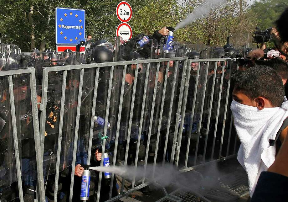 "Hungarian police use pepper spray on migrants at the ""Horgos 2"" border crossing into the Hungary, near Horgos, Serbia, Wednesday, Sept. 16, 2015. Small groups of migrants continued to sneak into Hungary on Wednesday, a day after the country sealed its border with Serbia and began arresting people trying to breach the razor-wire barrier, while a first group arrived in Croatia seeking another way into the European Union. (AP Photo/Darko Vojinovic) ORG XMIT: XDMV223 Photo: Darko Vojinovic / AP"