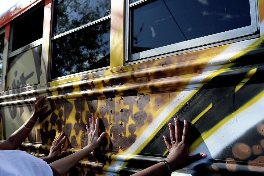 Girls in the Girl Zone after-school program and staff lay their hands on the newly painted bus during a non-denominational prayer at the Rock the Bus Mural Blessing and Unveiling with the Martinez Street Women's Center at Lockwood Park in San Antonio on Tuesday, Sept. 15, 2015.