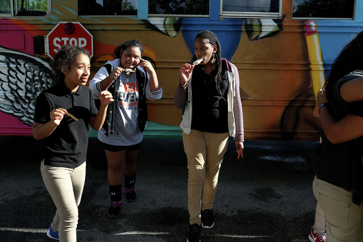 Girl Zone participants Yarili Marquez, 13, April Rodriguez, 14, and Ashlynn Spruell, 12, eat paletas at the conclusion of the Rock the Bus Mural Blessing and Unveiling with the Martinez Street Women's Center at Lockwood Park in San Antonio on Tuesday, Sept. 15, 2015.