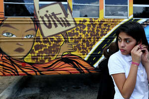 "Samantha Santibanez, 12, attends the Rock the Bus Mural Blessing and Unveiling with the Martinez Street Women's Center at Lockwood Park in San Antonio on Tuesday, Sept. 15, 2015. The Martinez Street Women's Center chose artist Ernesto Cuevas Jr. as the lead artist and designer and another artist, Rabbit Rye, an expert with spray paint, to design a mural for the Girl Zone program's bus. The Center held a ""Rock the Bus"" Paint Party on August 15 at Lockwood Park and then the artists finished the bus offsite and it was unveiled and used to transport the girls from school to the center for the first time on Tuesday.  The bus will transport girls, including Santibanez, from their schools to the Girl Zone after-school program and other educational activities for the girls at the Center."