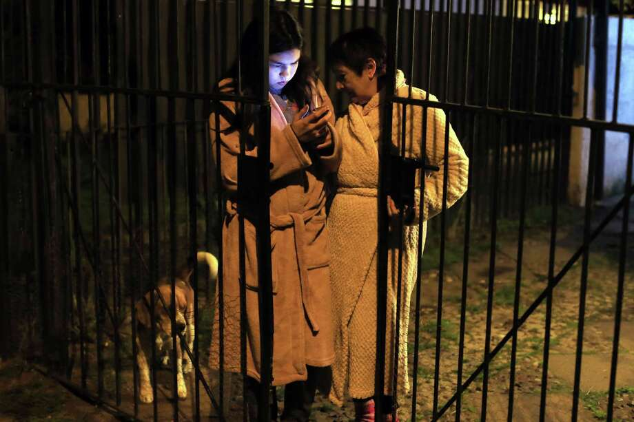 Women remain outside a building looking at a mobile phone during a strong quake in Santiago on September 16, 2015. A strong 7.2-magnitude earthquake struck the center of Chile on Wednesday, local seismologists said, triggering a tsunami alert, sparking panic and shaking buildings. AFP PHOTO /ALEJANDRO RUSTONALEJANDRO RUSTON/AFP/Getty Images Photo: ALEJANDRO RUSTON, Stringer / AFP / Getty Images / AFP