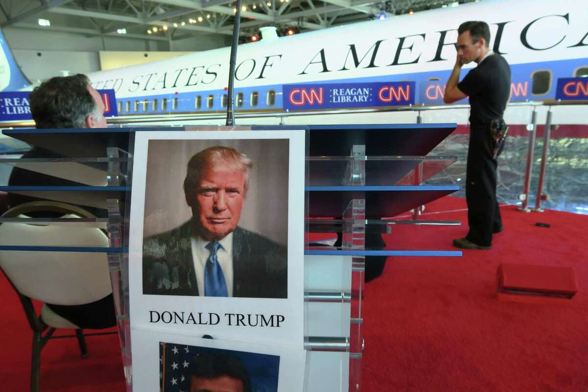 Technicians work behind the candidate podiums before the start of the CNN Republican presidential debates at the Ronald Reagan Presidential Library and Museum Wednesday, Sept. 16, 2015 in Simi Valley, Calif. (AP Photo/Tom Stathis)