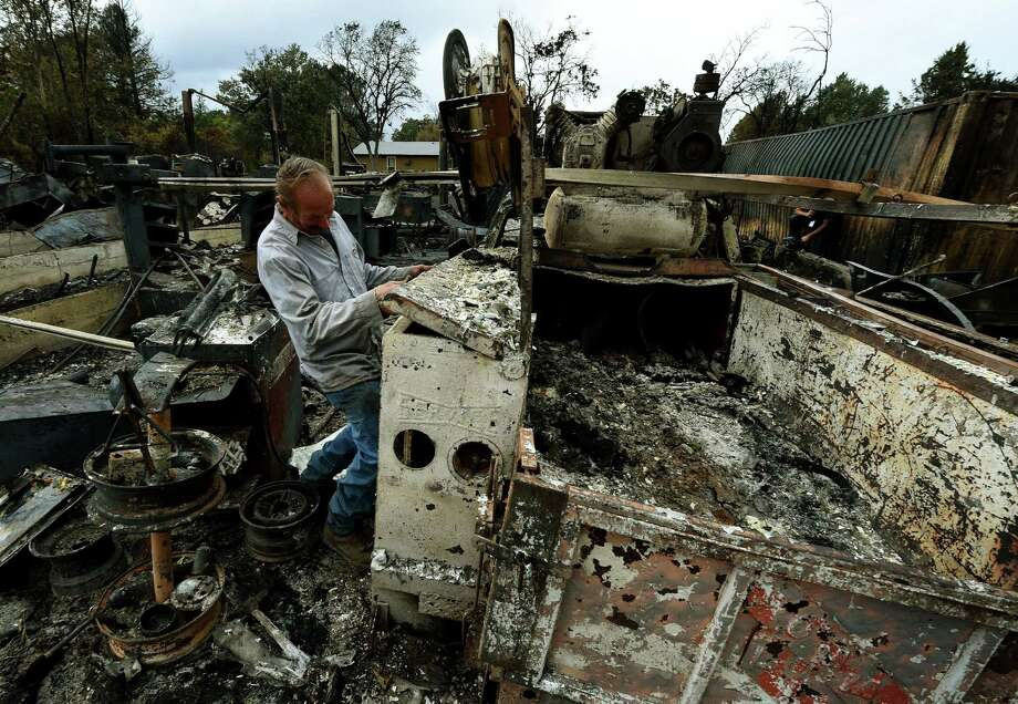 Business owner Larry Menzio looks at the remnants of his destroyed auto business after the Valley Fire swept through the town of Middletown, California, on September 16, 2015. The governor of California declared a state of emergency as raging wildfires spread in the northern part of the drought-ridden US state, forcing thousands to flee the flames.      AFP PHOTO / MARK RALSTONMARK RALSTON/AFP/Getty Images Photo: MARK RALSTON, Staff / AFP / Getty Images / AFP