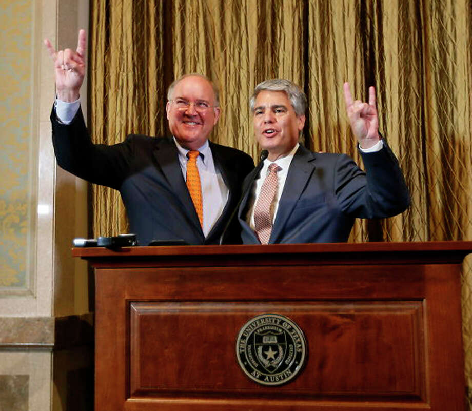"Interim athletic director Michael Perrin, left, and University of Texas President Gregory Fenves sign the ""hook em"" during a press conference, Wednesday, Sept. 16, 2015, announcing Steve Patterson's replacement after his departure the day before, at the University of Texas, in Austin, Texas. (Ricardo Brazziell /Austin American-Statesman via AP)  AUSTIN CHRONICLE OUT, COMMUNITY IMPACT OUT, INTERNET AND TV MUST CREDIT PHOTOGRAPHER AND STATESMAN.COM, MAGS OUT; MANDATORY CREDIT Photo: Ricardo Brazziell, MBO / Austin American-Statesman"