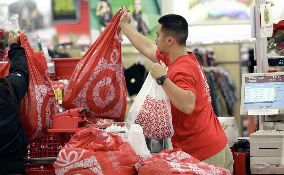 FILE - In this Nov. 23, 2012 file photo, a Target employee hands bags to a customer at the register at a Target store in Colma, Calif. Target executives on Wednesday, Sept. 16, 2015 said the company is handing out free Fitbit activity trackers to its more than 300,000 employees as the retailer tries to portray itself as a healthier place for both customers and workers. (AP Photo/Jeff Chiu, File) Photo: Jeff Chiu, STF / AP