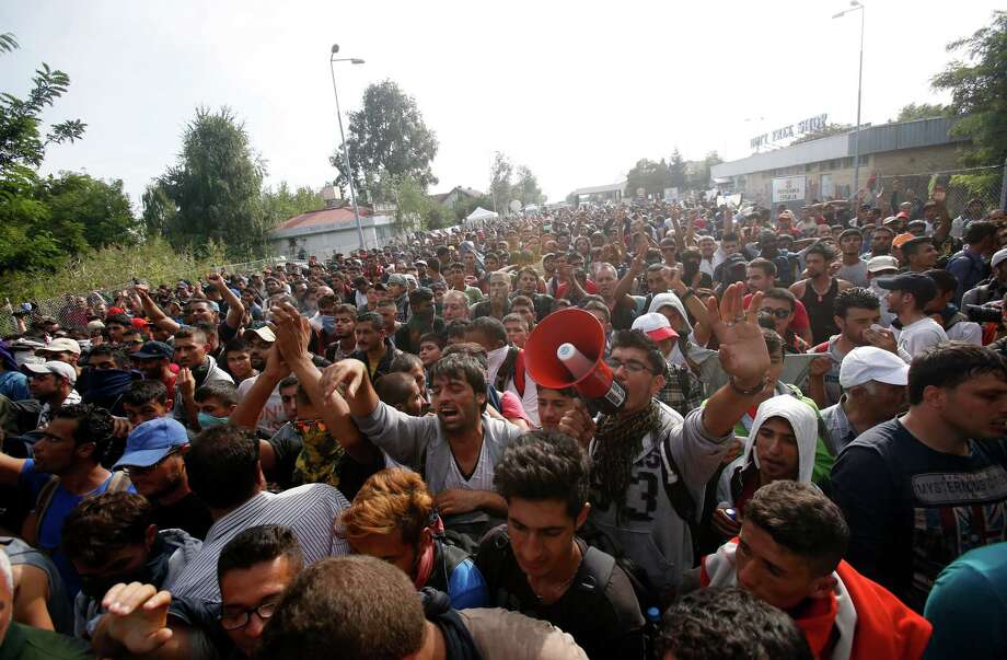 """Migrants protest at the """"Horgos 2"""" border crossing into the Hungary, near Horgos, Serbia, Wednesday, Sept. 16, 2015. Small groups of migrants continued to sneak into Hungary on Wednesday, a day after the country sealed its border with Serbia and began arresting people trying to breach the razor-wire barrier, while a first group arrived in Croatia seeking another way into the European Union. (AP Photo/Darko Vojinovic) Photo: Darko Vojinovic, STF / Associated Press / AP"""
