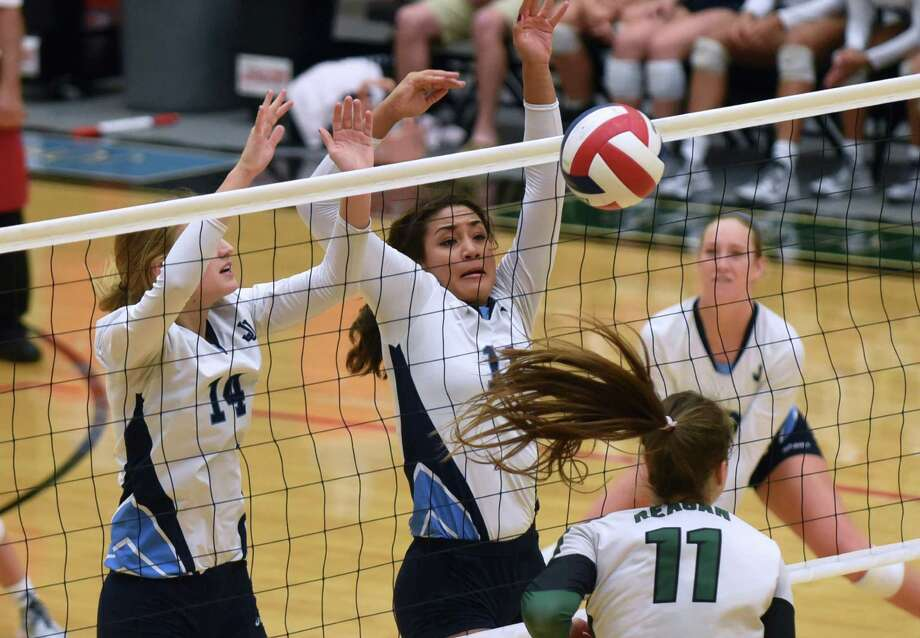 Payton Retzloff (14) and Adonica Wright of Johnson High School block a spike by Cameryn Ennis (11) of Reagan during volleyball action at Littleton Gym on Wednesday, Sept. 16, 2015. Photo: Billy Calzada, Staff / San Antonio Express-News / San Antonio Express-News