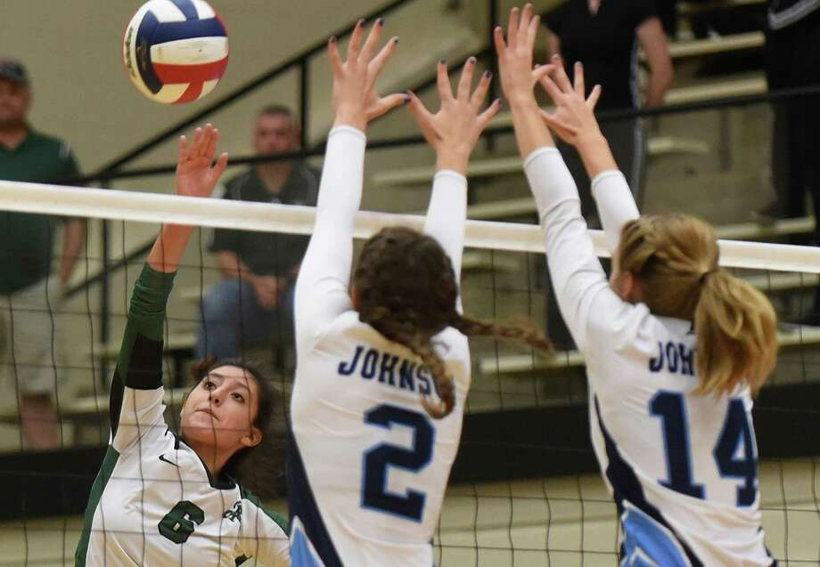Reagan's Elissa Barbosa tips the ball past Johnson's Lauren Bault (2) and Payton Retzloff (14) during the top-ranked Rattlers' three-set victory over the Jaguars at Littleton Gym. Photo: Billy Calzada / San Antonio Express-News / San Antonio Express-News