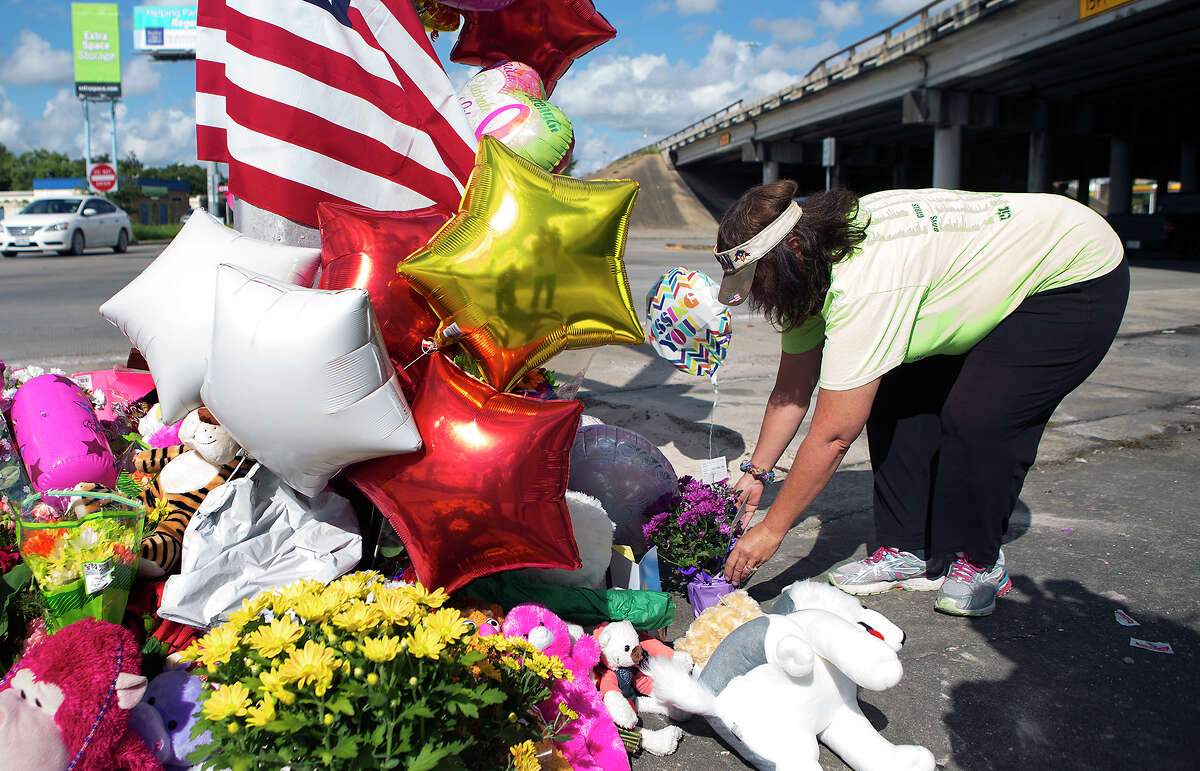 Lana Tabor places flowers at the scene of a vigil in the 4500 block of Telephone Road, Wednesday, Sept. 16, 2015, in Houston. Mourners created a vigil after a bus wreck that killed two HISD students early Tuesday morning.