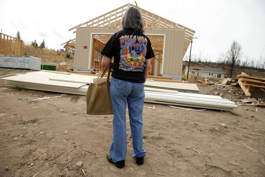 Top: Lillian Collins, who lost everything in the Boles Fire last year, checks on the progress of her new house in Weed. Photo: Scott Strazzante, The Chronicle