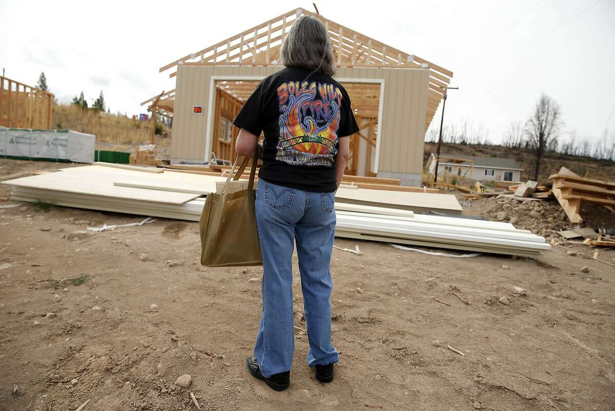 On the one year anniversary of the Boles Fire, Lillian Collins looks at the progress of her new house that is being built on the site of her home that was burned down during the Boles Fire in Weed, Calif.