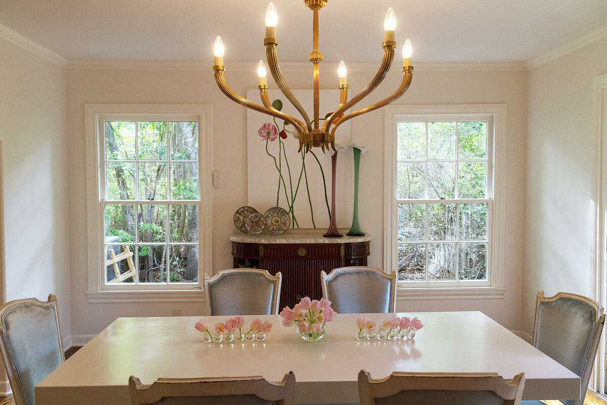 A custom-made table in white lacquer is surrounded by baby blue velvet chairs in the Terrell Hills home of Michael McLaughlin and Nicola Bathie, an interior designer and jewelery designer. The couple remodeled the house, in the neighborhood where both grew up, for their first home together.