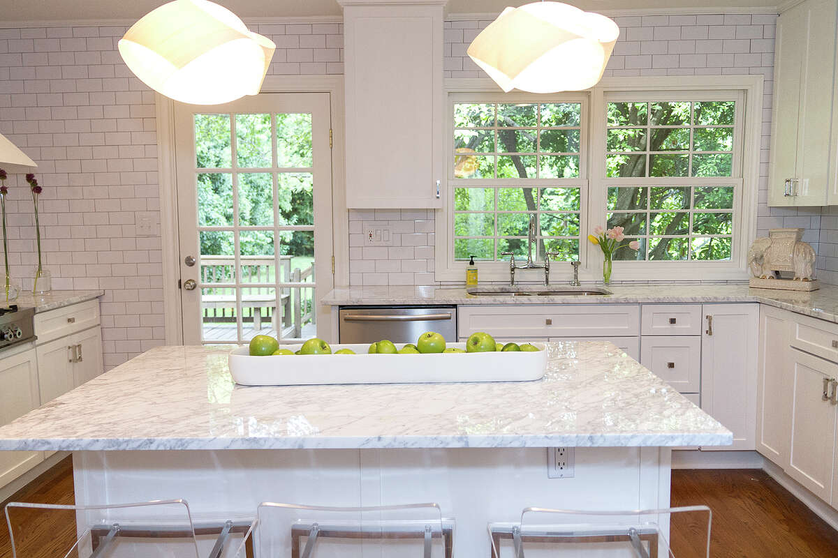 The predominately white palette extends to Michael McLaughlin and Nicola Bathie's kitchen, with subway tile on the walls and marble counters.