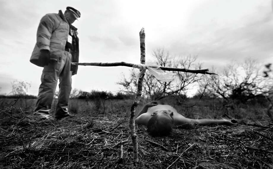 Rafael Hernandez, director of Angeles del Desierto stands over the body of an undocumented immigrant, after placing a cross he made of broken twigs.  Hernandez came across the body while searching on a ranch just outside Falfurrias, TX.   Wednesday Jan. 29, 2014. Photo: Bob Owen, Staff / San Antonio Express-News / ©2013 San Antonio Express-News