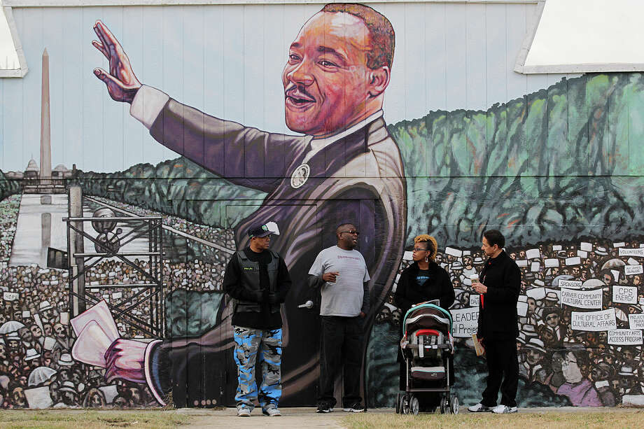 From left, H.J. Hill, Glenn Wilson, Elder Michelle Wilson and Arnold Bellow wait for the start of the annual City of San Antonio Martin Luther King, Jr. March in the city's Eastside, Monday, Jan. 19, 2015. The event drew over 100,000 participants that marched the 3-mile route ending at Pittman-Sullivan Park. The group was standing by the mural of their church, Greater Faith Institutional Church. Photo: JERRY LARA, Staff / San Antonio Express-News / © 2015 San Antonio Express-News