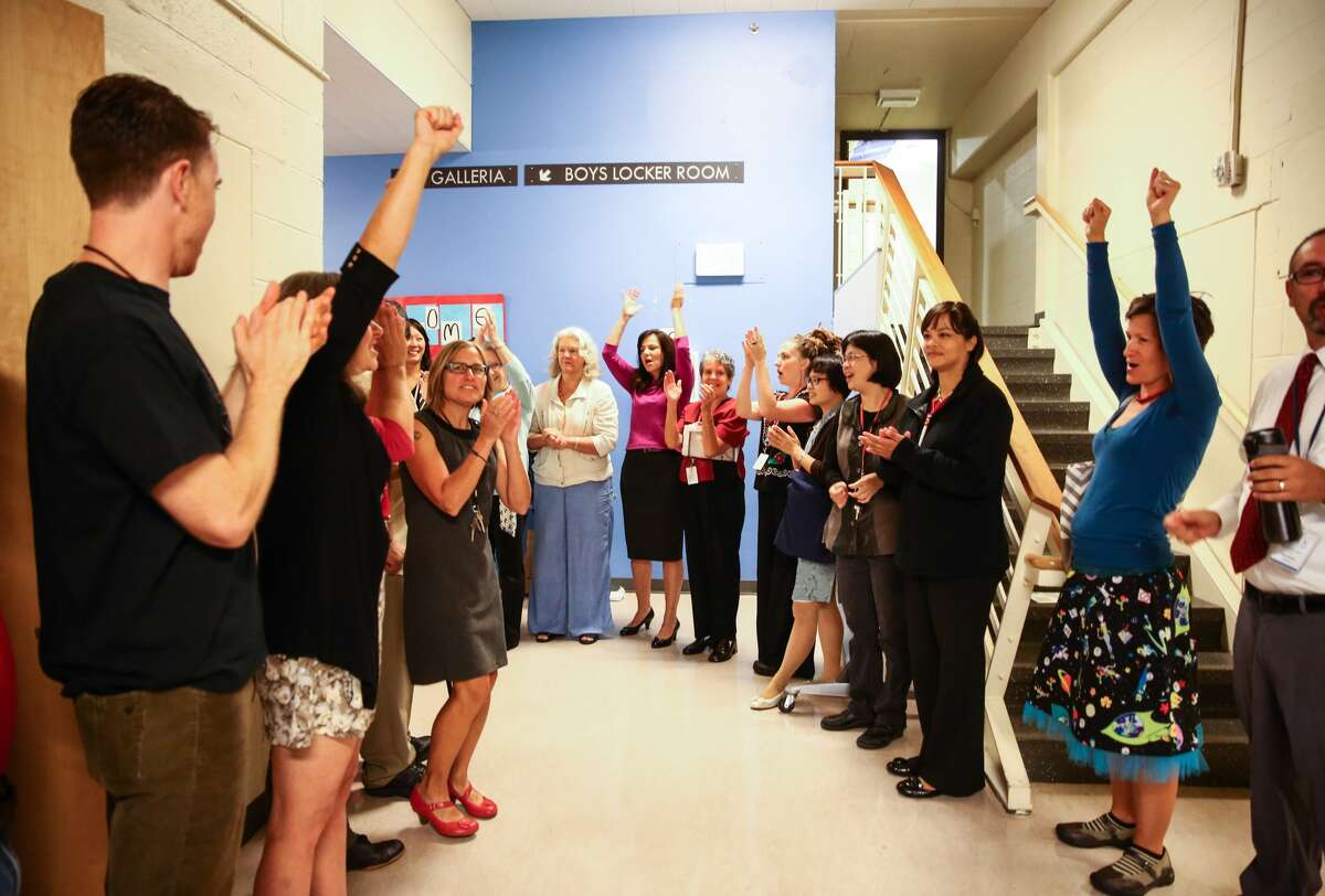 Staff at Chief Sealth International High School applaud the start of classes on Thursday, Sept. 17, 2015. Schools started a week late after a teachers strike.