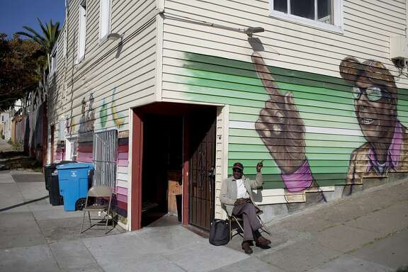Aloyd Davis, 83, waves to passersby under a mural of himself on the corner of Oakdale and Lane at Ford's Grocery in Bayview, San Francisco, Calif. on Friday, September 4, 2015.  Davis has sat outside the corner store almost every day for 15 years. (Photo by Tim Hussin)