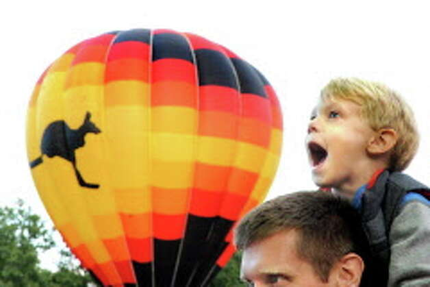 The Aussie Heir balloon is on display behind Lucas McCann, 3, of Queensbury as he gets a view from the shoulders of his father, Jason McCann, during the 42nd annual Adirondack Balloon Festival on Thursday, Sept. 18, 2014, at Crandall Park in Glens Falls, N.Y. (Cindy Schultz / Times Union) Photo: Cindy Schultz / 00028662A