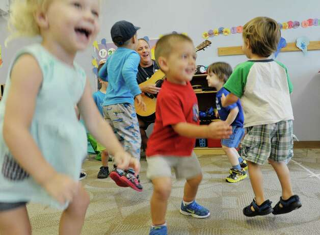 Children jump up and down as musician Andy Morse leads them in a song at Albany Med Kids Child Care on Wednesday, Sept. 9, 2015, in Albany, N.Y.   (Paul Buckowski / Times Union) Photo: PAUL BUCKOWSKI / 00033272A