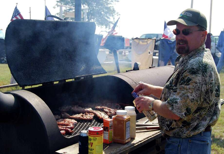 With meat on the grill and a variety of special seasonings at the ready, this Karnes County Lonesome Dove Fest cook-off contestant braves the September heat to prepare entries. Photo: Ralph Winingham /For The Express-News