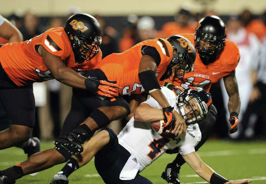 UTSA quarterback Blake Bogenschutz, bottom, is brought to the ground by Oklahoma State's Ryan Simmons, left, Jerel Morrow, center, and Josh Furman, right, during the second half of an NCAA college football game in Stillwater, Okla. Saturday, Sept. 13, 2014. Bogenschutz had 82 yards in the loss to Oklahoma State. (AP Photo/Brody Schmidt) Photo: BRODY SCHMIDT, FRE / Associated Press / FR79308 AP