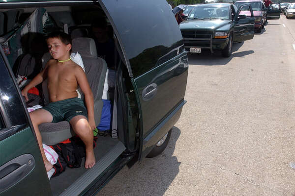Eight year-old Caleb Barton, of Beaumont,Tx, tries to stay cool in his mother's minivan Thursday as he and his family flee Hurricane RIta a few feet at a time along Northbound US Highway 96 near Silsbee, Tx. Beaumont Enterprise