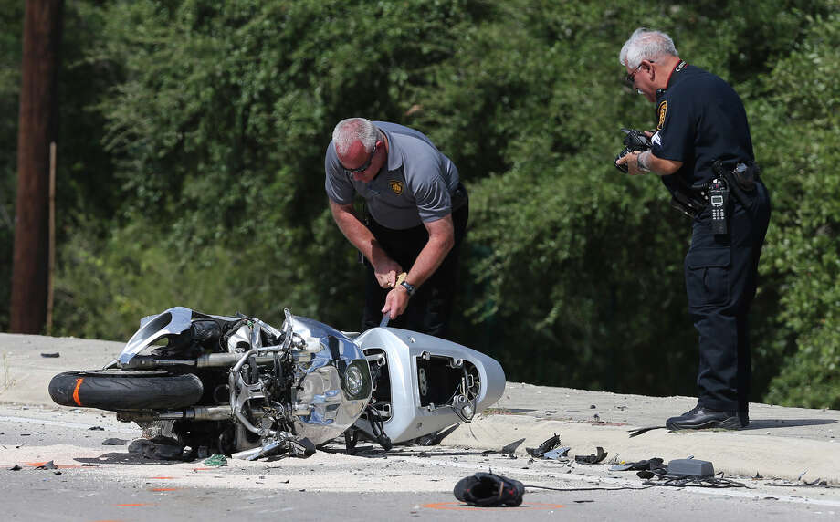 San Antonio police and fire personnel work Thursday September 17, 2015 at the scene of an accident involving a motorcycle and a pickup truck at about 2:15 p.m. at West Loop 1604 South and Wiseman Road. Patrolman Ricardo Perez said the 22-year-old male driver of a motorcycle collided with a grey Ford pickup truck that was making a turnaround on Loop 1604. After colliding, Perez said the driver of the motorcycle flew off his bike and hit the Sea World 151 sign and both of his legs were severed off. A police officer on his way to work was the first on the scene and applied a tourniquet. The injured man was transported from the scene by an Air Life helicopter and is in critical condition. Photo: John Davenport, Staff / San Antonio Express-News / ©San Antonio Express-News/John Davenport