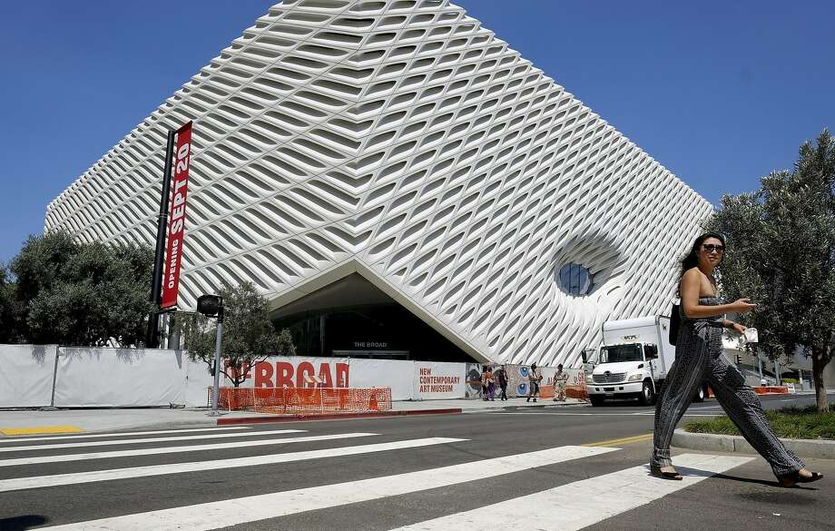 This Wednesday, Sept. 2, 2015 photo shows a pedestrian walking past the new Broad Museum in downtown Los Angeles. Billionaire philanthropist Eli Broad gives his latest gift to Los Angeles when The Broad, a $140 million museum built to hold some of the greatest pop-art works ever created, opens on Sept. 20, in the city's burgeoning downtown cultural center. Located across the street from the city's Museum of Contemporary Art and next door to its Walt Disney Concert Hall,The Broad contains some 2,000 pieces from its founder's personal collection. (AP Photo/Richard Vogel) Photo: Richard Vogel, Associated Press