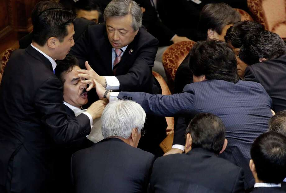 Opposition lawmakers in Japan's parliament used delaying tactics Thursday to block the committee from meeting to approve military expansion bills. Photo: Eugene Hoshiko, STF / AP
