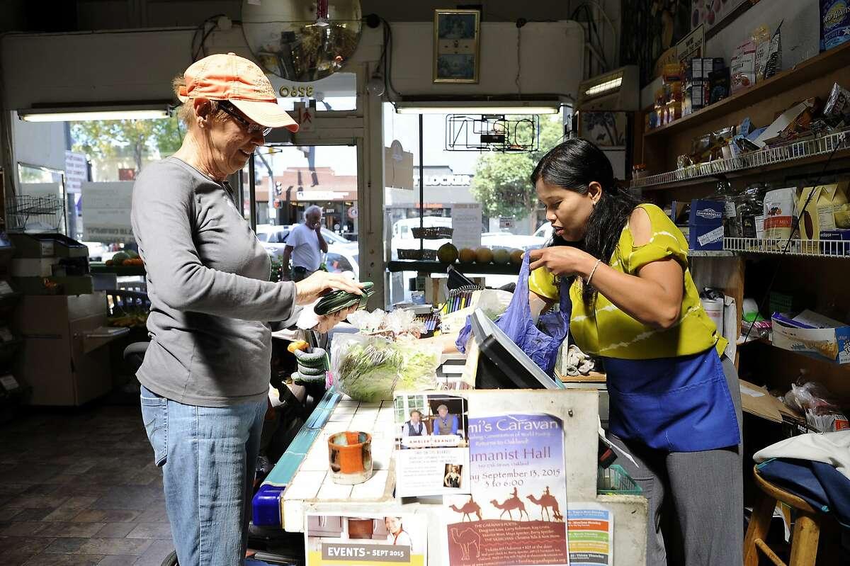 Owner Tey Uch, right, rings up customer Karen Martin of Martinez, as she shops at Lakeshore Produce on Lakeshore Blvd. in Oakland, CA Thursday, September 17, 2015.