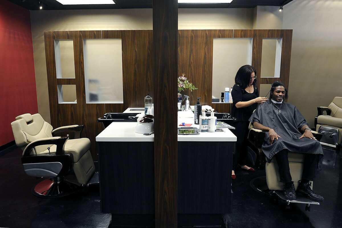 Stylist Maisah Mason gives customer Nate Anderson of Kennington, a 2 strand twist, at the 18/8 Fine Men's Salon on Lakeshore Blvd. in Oakland, CA Thursday, September 17, 2015.