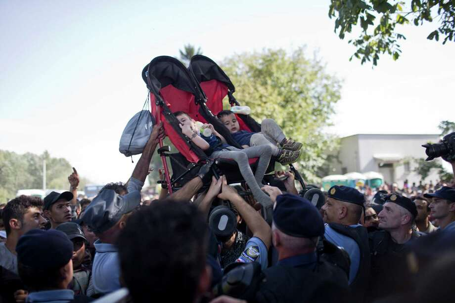 People lift two children as they try to get them to safety Thursday amid scuffles between migrants and police officers in Tovarnik, Croatia. Hundreds of migrants pushed through police lines  with people trampling and falling on each other. Photo: Marko Drobnjakovic, STR / AP