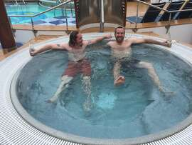 Tech executives John McKenney and Kris Taylor, of Philadelphia, lounge in the hot tub on the lido deck of Salesforce's floating Dream Boat hotel on Wednesday, Sept. 16, 2015. In spite of the cold and the rain, the two insisted on creating a cruise-like experience for themselves.
